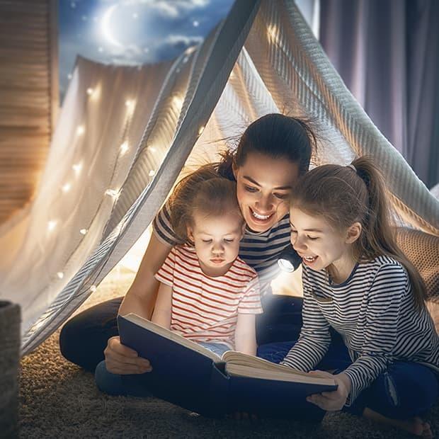 Mama leest voor aan 2 dochters onder een tent verlicht met sterretjes
